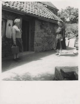 "Betty Tardif and Edith Gurnham outside a 300-year old inn ""Les Trois Fontaines,"" North coast of Jersey"